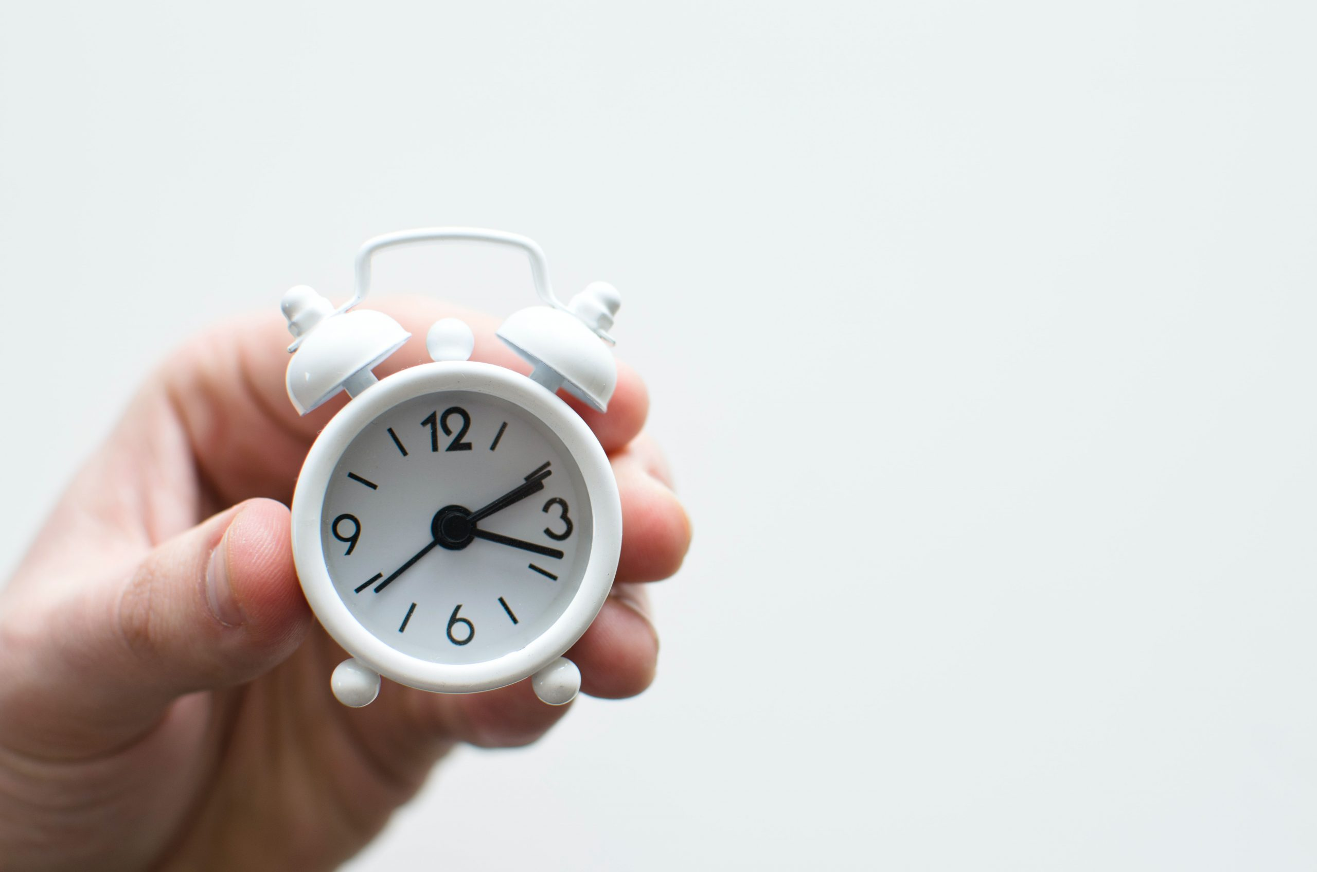 alarm clocking being held by a hand
