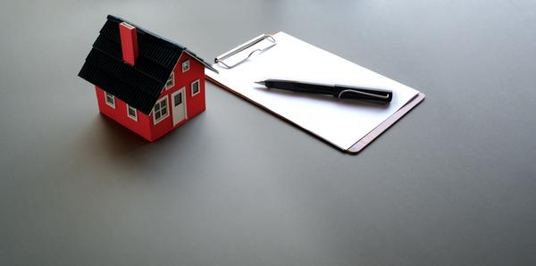 small house image with clipboard next to it.